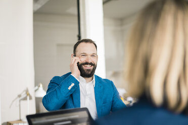 Smiling businessman on cell phone and businesswoman in office - JOSF01939