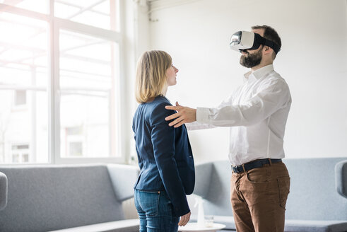 Businessman with VR glasses in office touching businesswoman - JOSF01942