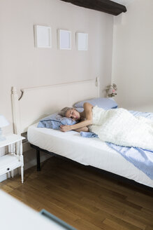 Pensive young woman lying in bed - GIOF03472