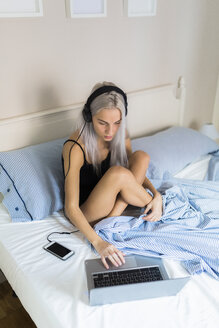 Young woman in bed with laptop and headphones - GIOF03487
