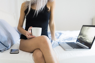 Young woman in bed with cup of coffee and laptop - GIOF03490