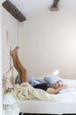 Young woman lying in bed with feet up - GIOF03499