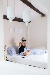 Young woman sitting in bed wearing VR glasses - GIOF03508
