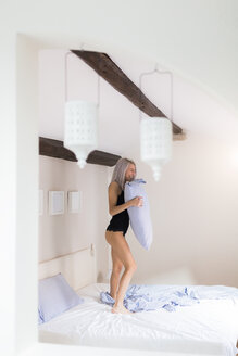 Happy young woman standing on bed - GIOF03514