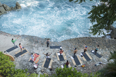 Mexico, Mismaloya, instructor with yoga class at ocean front - ABAF02182