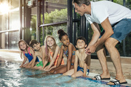 Instructor talking to children sitting on poolside in indoor swimming pool - MFF04147