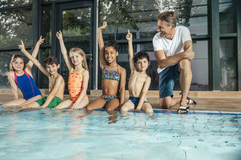 Children with instructor on poolside in indoor swimming pool raising their hands - MFF04150