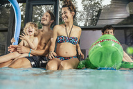 Happy family sitting on poolside in indoor swimming pool - MFF04153