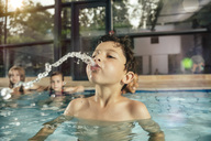 Boy with friends in indoor swimming pool spitting water - MFF04159