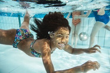 Portrait of smiling girl under water in swimming pool - MFF04174