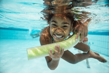 Portrait of smiling girl with pool noodle under water in swimming pool - MFF04180