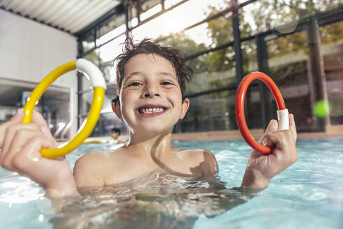Portrait of proud boy holding two diving rings in swimming pool - MFF04183