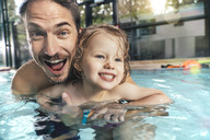 Portrait of happy father with daughter in indoor swimming pool - MFF04186