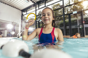Portrait of proud girl holding diving ring in swimming pool - MFF04201