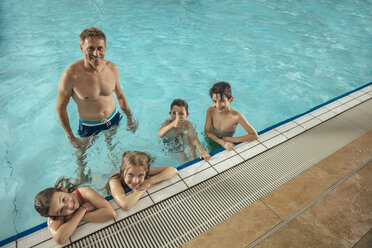 Portrait of smiling children with instructor in indoor swimming pool - MFF04204