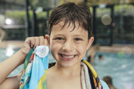 Portrait of proud boy showing his swimming badge at the poolside of an indoor swimming pool - MFF04216