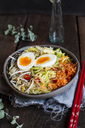Bowl of glutenfree Udon noodle soup with carrots, Chinese cabbage, zoodles, mungo beans sprouts and boiled egg - SBDF03384