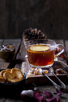 Glass of black tea with slice of lemon and rock sugar on wooden table - SBDF03386