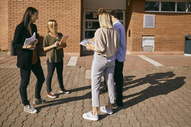 Group of students standing outdoors with documents - ZEDF00998