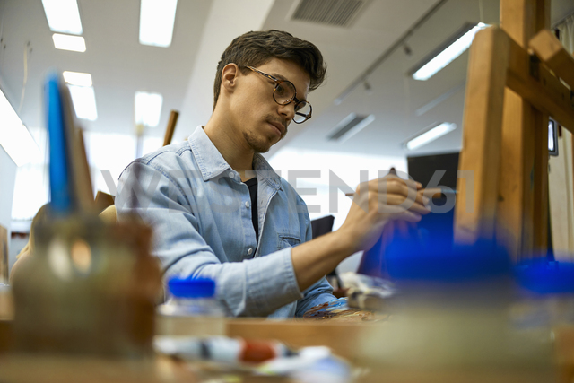 Student painting on easel in art class - ZEDF01010