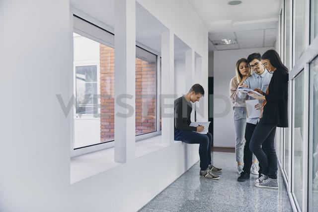 Group of students standing in hallway with documents - ZEDF01025 - Zeljko Dangubic/Westend61