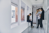 Group of students standing in hallway with documents - ZEDF01025