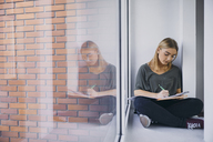 Student sitting at the window in hallway learning - ZEDF01028