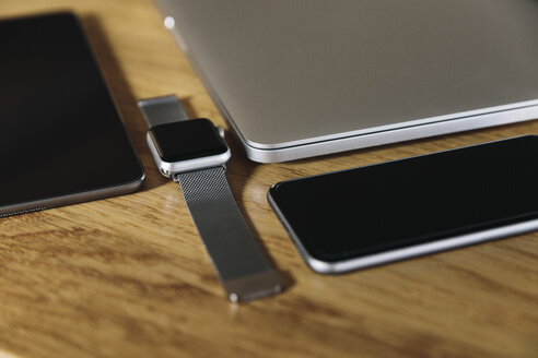 Tablet, smartwatch, smartphone, and  laptop on wood - MFF04223