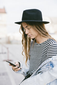 Portrait of fashionable young woman wearing hat using smartphone - GIOF03531