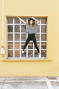 Fashionable young woman wearing hat jumping in the air - GIOF03537