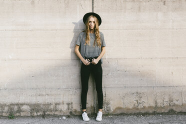 Fashionable young woman wearing hat leaning against concrete wall - GIOF03540