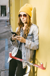 Portrait of fashionable young woman with bicycle leaning against facade using cell phone - GIOF03546
