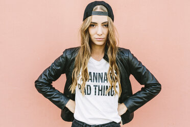 Portrait of fashionable young woman wearing black baseball cap and leather jacket - GIOF03552