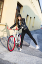 Fashionable young woman with bicycle - GIOF03555