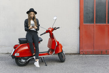 Fashionable young woman sitting on red motor scooter using cell phone - GIOF03558