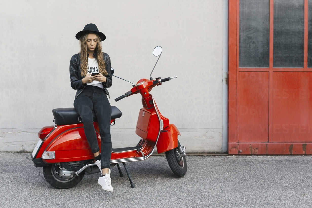 Fashionable young woman sitting on red motor scooter using cell phone - GIOF03558 - Giorgio Fochesato/Westend61