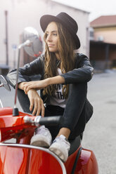 Portrait of fashionable young woman sitting on red motor scooter - GIOF03561