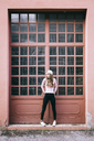 Fashionable young woman standing in front of entrance gate - GIOF03564