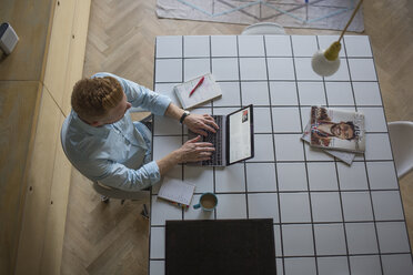 Freelance businessman working on his laptop at home - MOMF00305