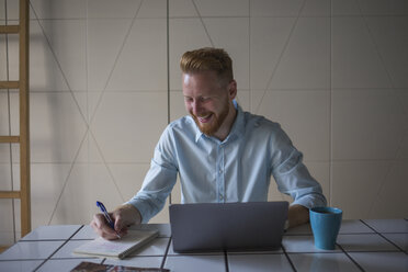 Laughing freelance businessman working on his laptop at home - MOMF00308