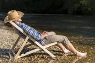 Man relaxing in beach chair at riverside - STSF01437