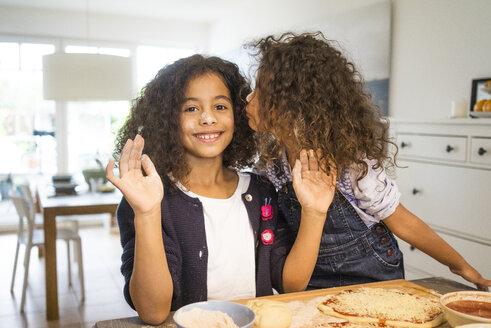 Little girl kissing sister in kitchen, baking pizza - MOEF00315