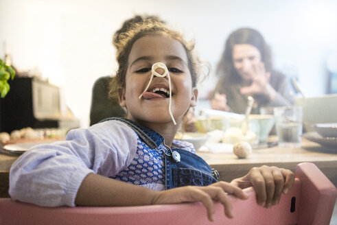 Portrait of a cheeky little girl eating spaghetti - MOEF00318