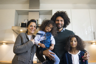 Happy family standing in kitchen, laughing - MOEF00324