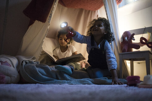 Two sisters sitting in dark children's room, playing with torch, reading book - MOEF00336