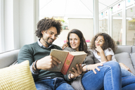 Happy family sitting on couch, reading book - MOEF00351