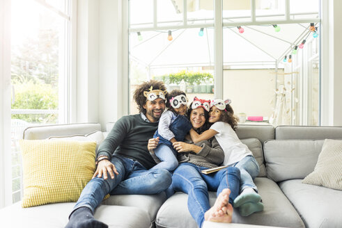 Happy family sitting on couch, wearing animal masks - MOEF00357