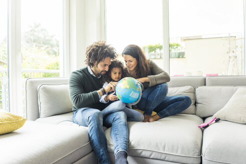 Happy family sitting on couch with globe, daughter learning geography - MOEF00363