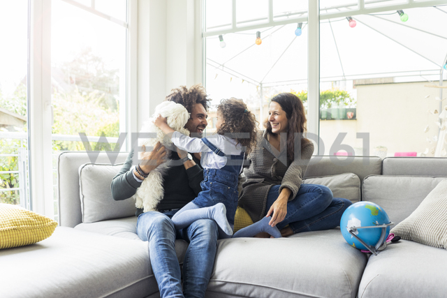 Happy family with dog sitting together in cozy living room - MOEF00366 - Robijn Page/Westend61