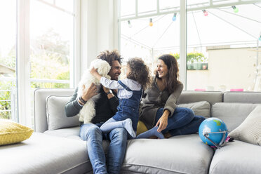 Happy family with dog sitting together in cozy living room - MOEF00366